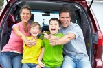 Family in back of SUV giving an Auto Repair thumbs up