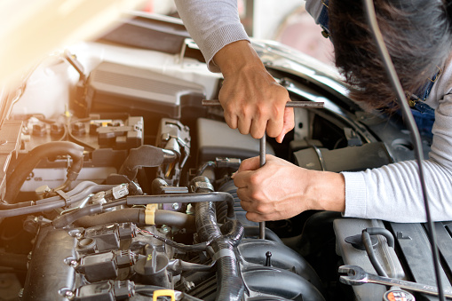 Auto mechanic working in garage. Dodge Repair service.